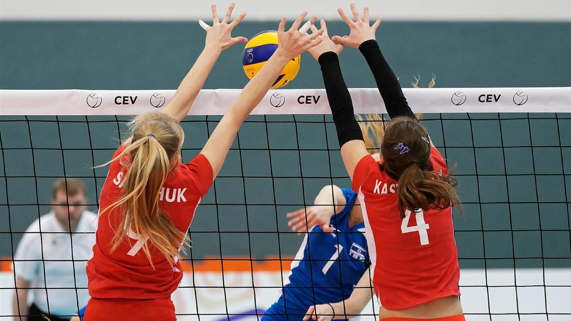 Women spiking and blocking while playing volleyball.